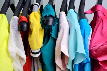 casual clothes: mujer multicolor ropa que cuelga en la percha verticalclothing colores pastel colgando de la percha horizontal Foto de archivo