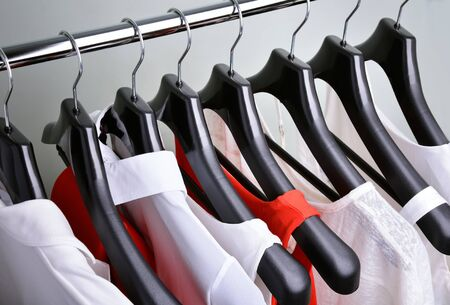 white clothing: white and coral womens clothing hanging top view horizontal frame Stock Photo