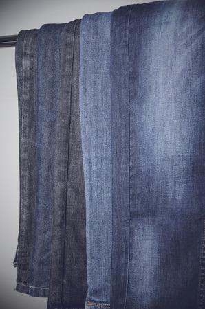 vertically: Jeans hanging vertically on a hanger. vertical frame