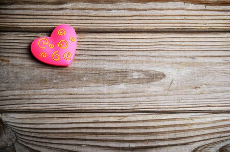 pink heart on a wooden background. horizontal frame