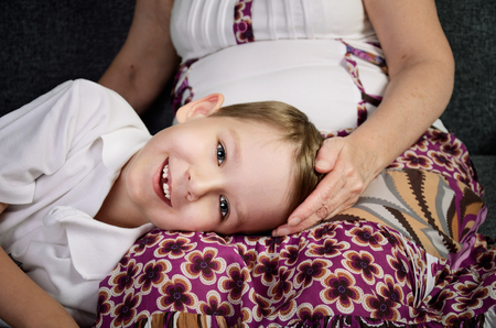happy teenagers: laughing little boy looking at camera and his loving grandmother. horizontal