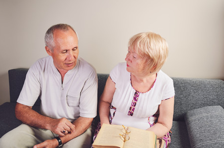 older man and woman 60-65 years old talking, discussing book. horizontal Stockfoto