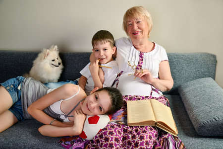 Grandma with grandchildren smiling sitting on the couch horizontal Stock Photo