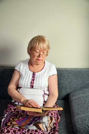 elderly woman reading a book sitting on the couch vertical format