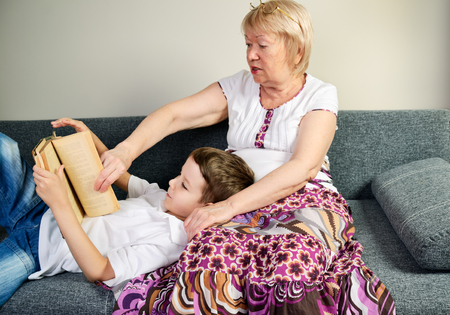 boy reading a book with his grandmother indoor horizontal Stock Photo