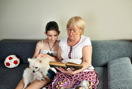 granddaughter sit next to her grandmother on the couch and read a book horizontal Stockfoto