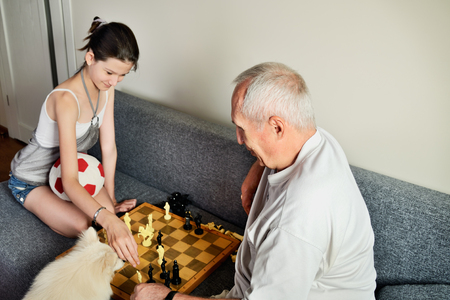 affectionate action: smiling granddaughter and grandpa playing chess horizontal Stock Photo