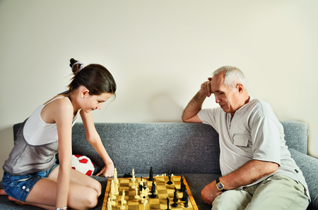 affectionate action: granddaughter and grandpa playing chess front view horizontal Stock Photo