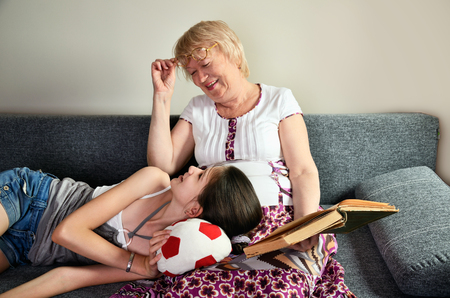 Grandmother and granddaughter laughing sit on the couch and looking at each other horizontal Stock Photo