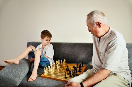 chess men: grandson and grandpa playing chess horizontal