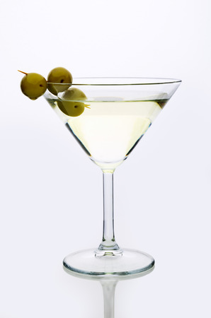 martini: glass martini with olive  light background vertical Stock Photo