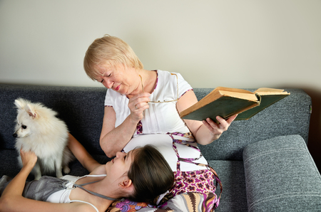 Grandmother and granddaughter with the dog laughing sit on the couch and looking at each other horizontal