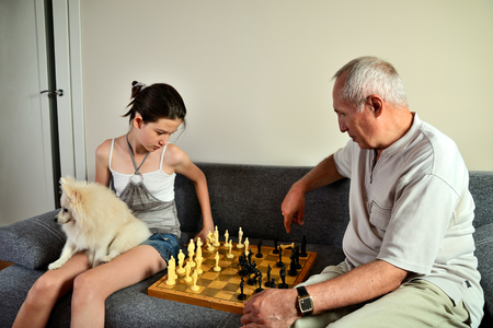 affectionate actions: granddaughter with a dog and grandpa playing chess horizontal