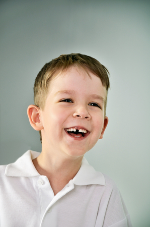laughing boy portrait. the boy opened his mouth and lost a tooth. vertical format