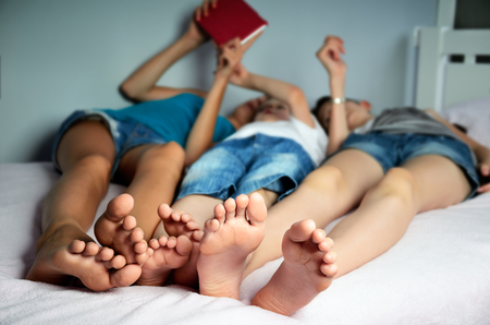 down: children are lying on the bed and play on the tablet. their legs in the foreground close-up. focus on the feet. horizontal