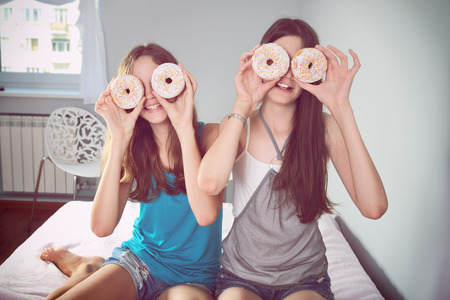 children face: Two teen girls having fun with donuts. tinted image. horizontal