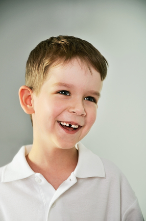 cheerful cute boy portrait. the boy opened his mouth and lost a tooth. vertical