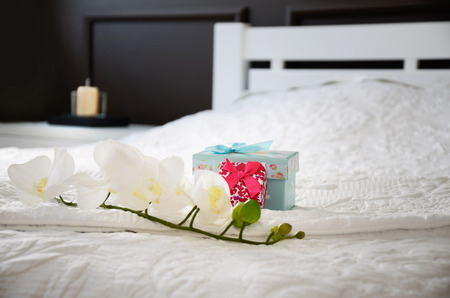 orchid flower and gift boxes on the bed in the bedroom. horizontal, focus on the pink giftbox