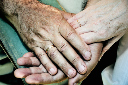 hand: tinted color image of old married couples hands. horizontal format