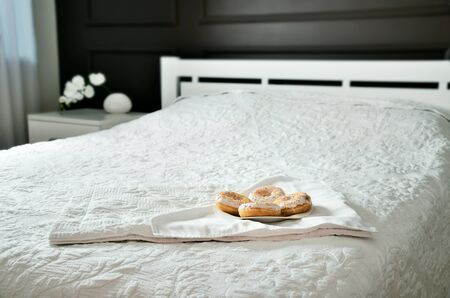 horizontal format: donuts in the plate on a bed in a bedroom. horizontal format