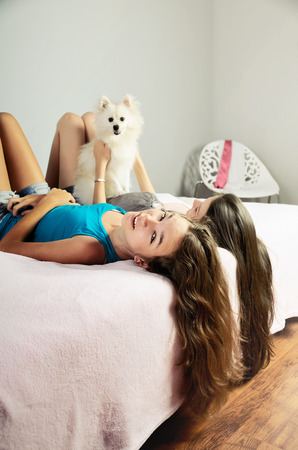 pat down: two girls playing with a Pomeranian on the bed. vertical format Stock Photo