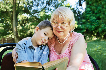 smiling boy and his grandmother reading a book in the park. horizontal Stock Photo