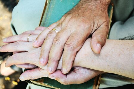 horizontal format: elderly mans and womans hands. horizontal format
