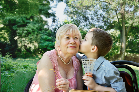 affectionate actions: grandson hugs and kisses on the cheek his grandmother. horizontal