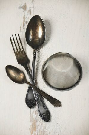 German silver spoon, fork and other utensils on a white wooden background vertical format