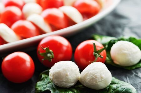 horizontal format: mozzarella cheese balls, ripe cherry tomatoes and caprese salad in a dish on the dark background close-up. horizontal format