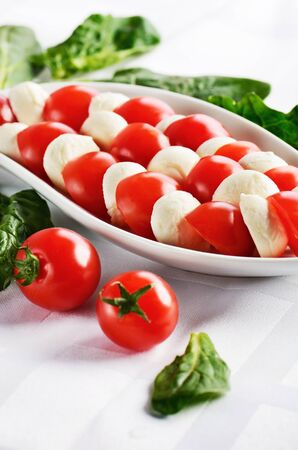 vertical format: dish with sliced mozzarella cheese balls and ripe cherry tomatoes in caprese salad on the white table. vertical format