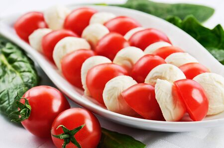 horizontal format: dish with sliced mozzarella cheese balls and ripe cherry tomatoes in caprese salad on the white table. horizontal format Stock Photo