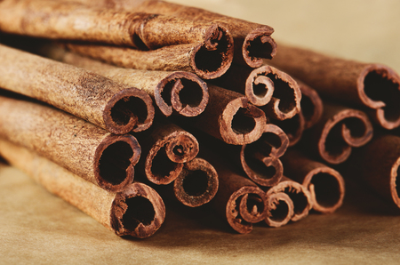 christmas grounds: cinnamon sticks on paper background close-up horizontal format Stock Photo