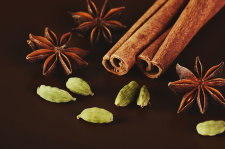 two cinnamon sticks, three stars anise and a cardamom on a brown background close-up horizontal format