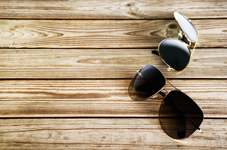 unisex: two unisex sunglasses on a wooden background top view horizontal