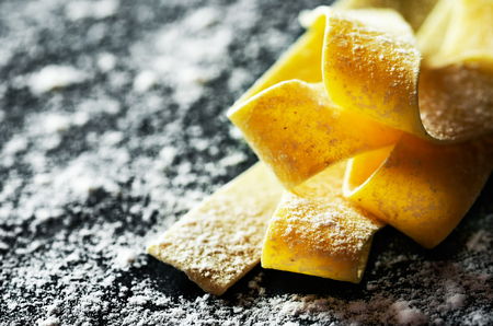 handmade pasta at side on a dark with flour background close-up horizontal format Stock Photo