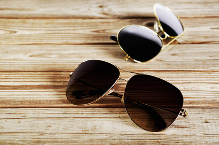 unisex: two unisex sunglasses close-up on a wooden background top view horizontal