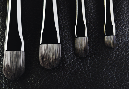 four makeup brushes close-up on a textured black leather background. horizontal format