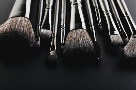 Makeup brushes set close-up on a black background horizontal format, space for text