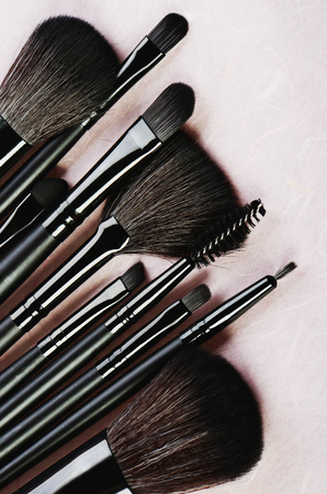 Makeup brushes set on a light pink background vertical format, space for text Banco de Imagens