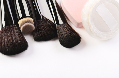 Makeup brushes, sponge and powder puff on a white background horizontal format, space for text Banco de Imagens
