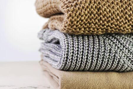 three warm sweaters are stacked on the table on a light background horizontal