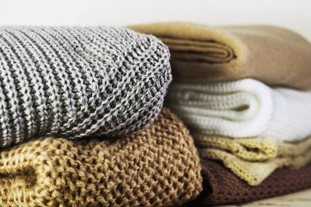 two stacks of warm sweaters on the table on a light background horizontal Stock Photo