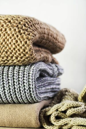 warm sweaters are stacked on the table on a light background vertical