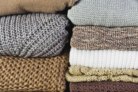 front view two stacks of warm sweaters on a full background horizontal Stock Photo