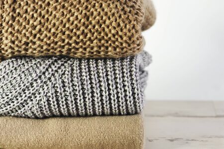 three warm sweaters in a stack on a white wooden shelf on a light background, front view, close-up, horizontal