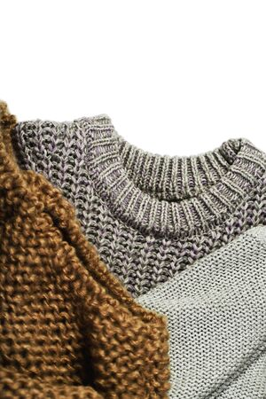 three warm sweaters isolated on white background, vertical