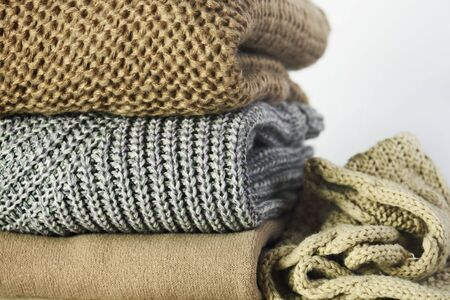 three warm sweaters and a scarf in a stack on a white wooden shelf on a light background, front view, close-up, horizontal