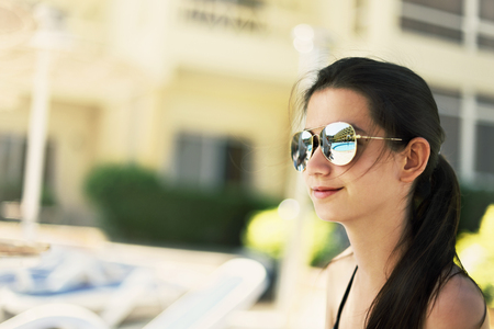 tinted image pretty smiling girl sitting a poolside. swimming pool and the hotel building are reflected in her sunglasses Stock Photo