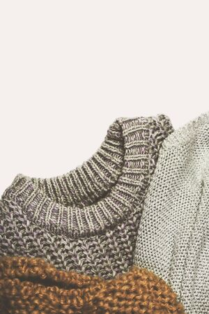 tinted image three warm sweaters on lighte background, vertical Stock Photo